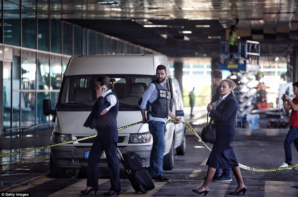 Um membro dos serviços de segurança coloca um cordão de isolamento no lugar onde um dos homens-bomba se explodiu como o aeroporto retorna ao normal