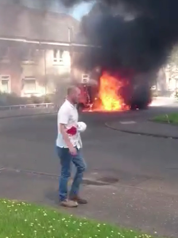 Man soaked in blood walks past burning vans