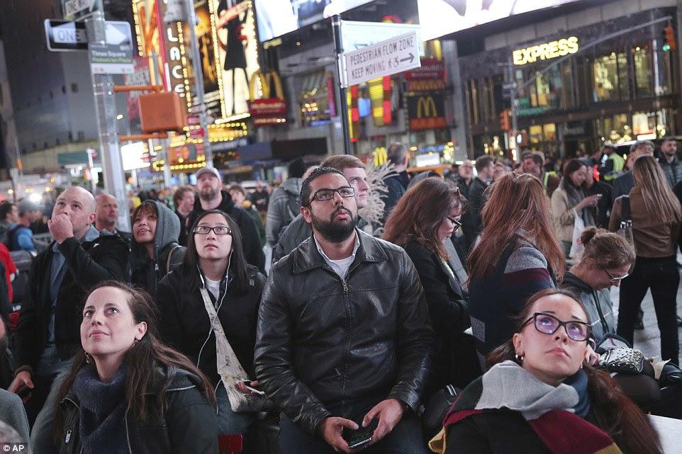 Pedestres assistir os resultados das eleições em telas grandes em Times Square, Nova York, na terça-feira