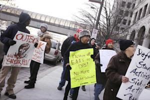 Protesters stand outside Cadillac Place, Monday, Jan. …