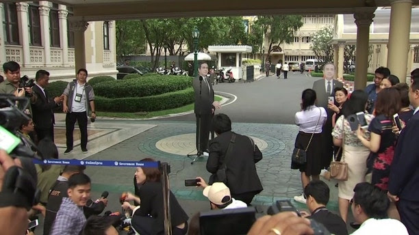 """In this image from video, a life-sized cardboard cut-out figure of Thailand's Prime Minister Prayuth Chan-ocha, stands next to the microphone and faces the media after the Prime Minister left the sce   ne, in Bangkok, Thailand, Monday Jan. 8, 2018.  Prayuth evaded questions by bringing out a life-sized cardboard cut-out of himself, and telling reporters to """"ask this guy"""" if they had """"any questions on politics or conflict"""", he then turned on his heel and walked off, leaving the mock-up behind, to bemused looks and awkward laughter from the assembled media. (TPBS via AP)"""