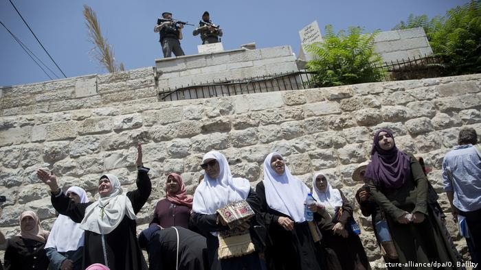 Palestinian women come together to pray outside of the holy site, in the Old City of Jerusalem.
