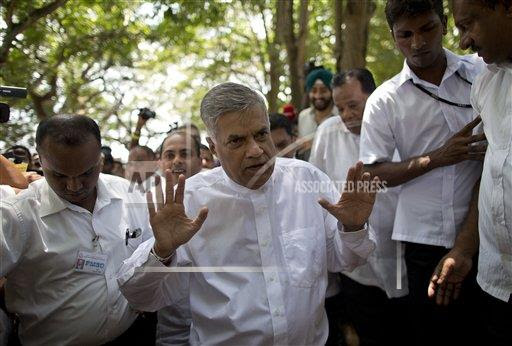 Sri Lankan Prime Minister Ranil Wickremasinghe, center, gestures outside a polling station after casting his vote in Colombo, Sri Lanka, Monday, Aug. 17, 2015. Sri Lankans voted in Parliamentary elections on Monday that will decide the political future of a former strongman leader seeking a comeback eight months after being unseated in a shocking election defeat.