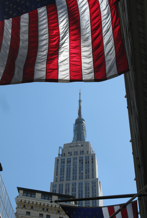the top of the Empire State Building as seen between buildings and flags, Manhattan, NYC