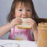 Girl eating a peanut butter sandwich.