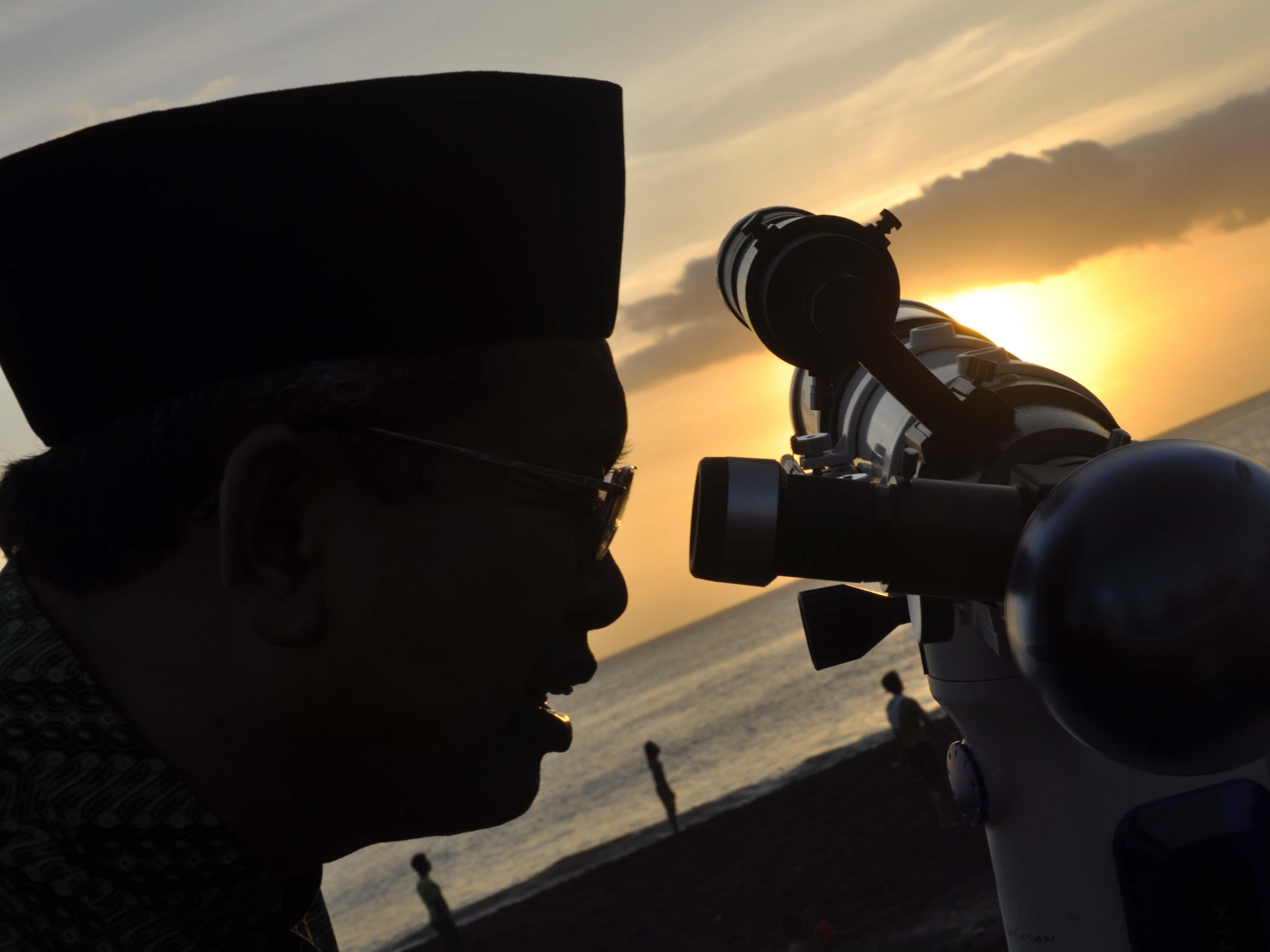 RUKYATUL HILAL. Seorang petugas berusaha melihat hilal dengan teropong bulan di Pantai Loang Baloq, Ampenan, Mataram, Minggu (31/7).