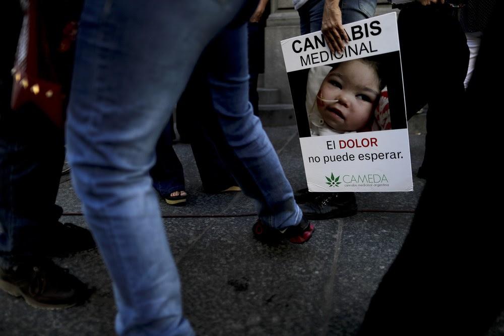 Mulher segura cartaz com mensagem a favor do uso terapêutico da cannabis nesta quarta-feira (29) do lado de fora do Senado da Argentina (Foto: AP Foto/Natacha Pisarenko)