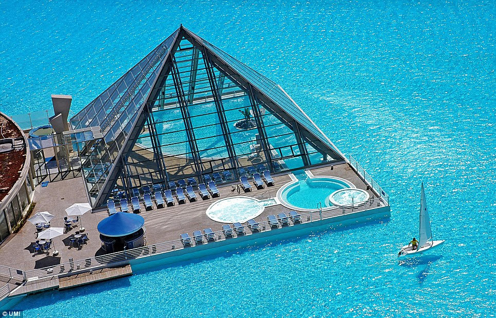 Dazzling blue: A small boat sails round a platform jutting into the lagoon's 20-acre expanse