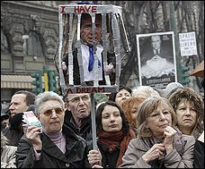 As thousands demonstrate in Milan, Italian Prime Minister Silvio  Berlusconi is depicted as behind bars.