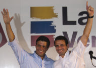 Opposition politician Leopoldo Lopez, left, and Henrique Capriles Radonski acknowledge supporters at a news conference in Caracas, Venezuela, Tuesday Jan 24, 2012. Lopez bowed out of Venezuela's presidential race on Tuesday, saying he will support front-runner Capriles. The announcement gives a significant boost to Capriles, who has a commanding lead in the polls ahead of the Feb. 12 opposition primary, which will choose a single challenger to face President Hugo Chavez in the Oct. 7 presidential election. (AP Photo/Ariana Cubillos)