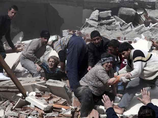 Feridos são retirados de prédios em escombros na cidade de Van após o terremoto deste domingo (23) (Foto: Reuters)
