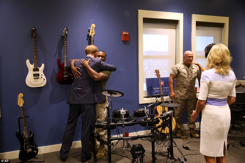 Comrades embrace: US Marine Sergeant and Prince Harry - who served as Captain Harry Wales in the UK Army Air Corps, flying Apaches against the Taliban - meet in the music room of the USO Warrior and Family Center at Fort Belvoir, Virginia, while First Lady Michelle Obama and Dr Jill Biden meet US Marine Colonel Shane Tomko