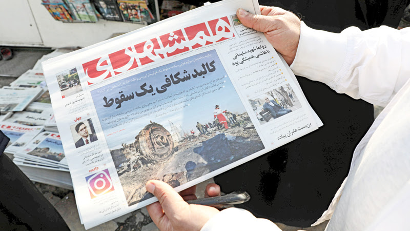 An Iranian holds a newspaper with a picture of the debris of the Ukrainian plane that crashed in Tehran earlier this week, outside a news stand in the Islamic republic's capital on Saturday. - AFP