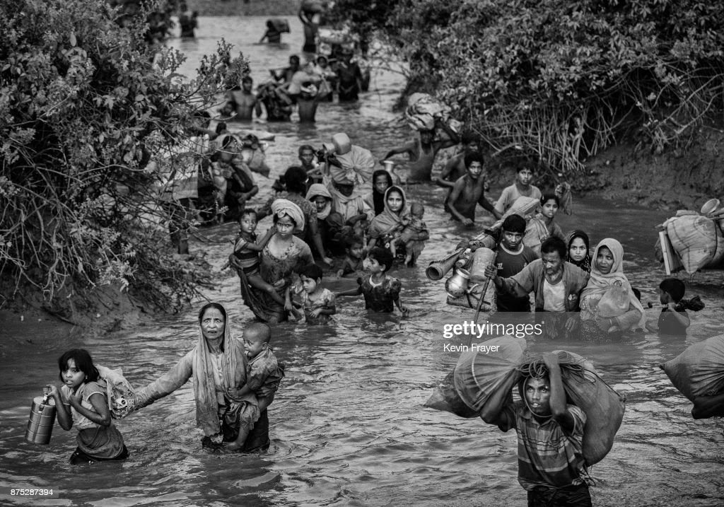 COX'S BAZAR, BANGLADESH - NOVEMBER 01: Rohingya Muslim refugees crowd a canal as they flee over the border from Myanmar into Bangladesh at the Naf River on November 1, 2017 near Anjuman Para in Cox's Bazar, Bangladesh. More than 600,000 Rohingya refugees have flooded into Bangladesh to flee an offensive by Myanmar's military that the United Nations has called 'a textbook example of ethnic cleansing'. The refugee population continues to swell further, with thousands more Rohingya Muslims making the perilous journey on foot toward the border, or paying smugglers to take them across by water in wooden boats. Hundreds are known to have died trying to escape, and survivors arrive with horrifying accounts of villages burned, women raped, and scores killed in the 'clearance operations' by Myanmar's army and Buddhist mobs that were sparked by militant attacks on security posts in Rakhine state on August 25, 2017. What the Rohingya refugees flee to is a different kind of suffering in sprawling makeshift camps rife with fears of malnutrition, cholera, and other diseases. Aid organizations are struggling to keep pace with the scale of need and the staggering number of them - an estimated 60 percent - who are children arriving alone. Bangladesh, whose acceptance of the refugees has been praised by humanitarian officials for saving lives, has urged the creation of an internationally-recognized 'safe zone' where refugees can return, though Rohingya Muslims have long been persecuted in predominantly Buddhist Myanmar. World leaders are still debating how to confront the country and its de facto leader, Aung San Suu Kyi, a Nobel Peace Prize laureate who championed democracy, but now appears unable or unwilling to stop the army's brutal crackdown.