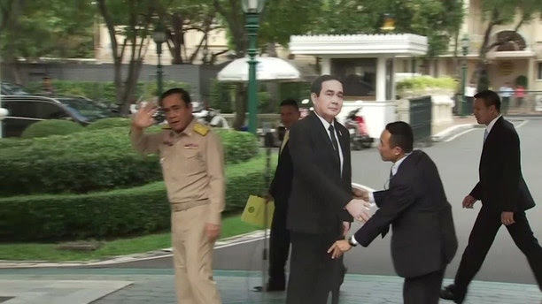 """In this image from video, Thailand's Prime Minister Prayuth Chan-ocha, left, waves and walks off as a life-sized cardboard cut-out figure of himself is placed next to the microphone during a media conference in Bangkok, Thailand, Monday Jan. 8, 2018.  Prayuth evaded questions by bringing out a life-sized cardboard cut-out of himself, and telling reporters to """"ask this guy"""" if they had """"any questions on politics or conflict"""" then turned on his heel and walked off, leaving the mock-up behind, to bemused looks and awkward laughter from the assembled media. (TPBS via AP)"""