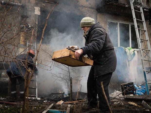 Moradores tentam salvar seus pertences em um prédio destruído após conflitos entre rebeldes pró-russos e forças ucranianas em Donetsk (Foto: Audrey Borodulin/AFP)