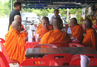 Family members serve food to the Monks