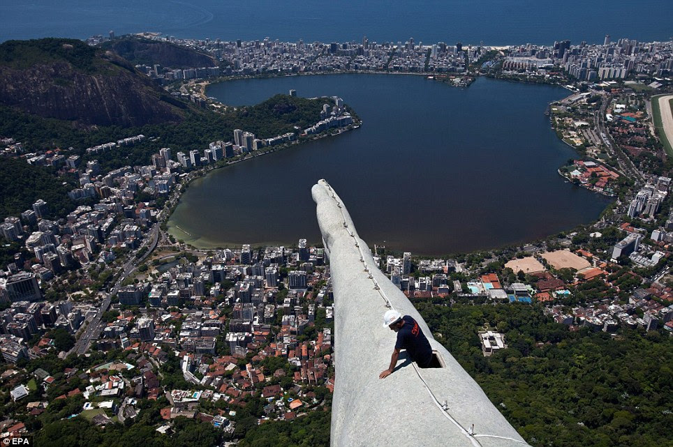 Arm with a view: A construction worker can be seen on the arm of the famous statue which is 100ft tall
