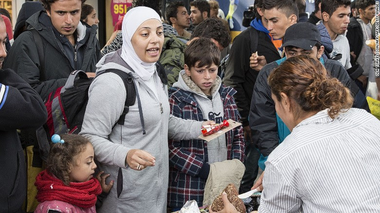 Volunteers hand food and drink to refugees arriving at Malmo station in Sweden in September 2015.
