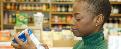 A woman reading the nutrition label of a prepared food item.