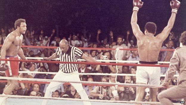 Muhammad Ali, arms raised in victory, walks to his corner as referee Zack Clayton counts out George Foreman after Ali knocked him down in the eighth round of their Rumble in the Jungle