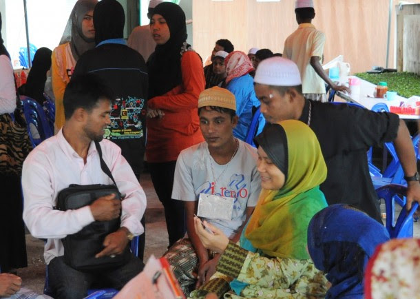 Rohingya refugee Sakir Husan, center in yellow prayer cap, sits surrounded by well-wishers at a house in the capital of southern Thailand's Pattani Province. (Photo: Joe Jackson / The Irrawaddy)