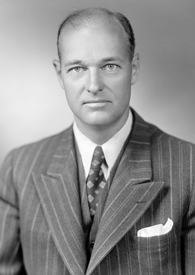 Head and shoulders portrait of a dignified man in his forties, wearing a suit and tie.