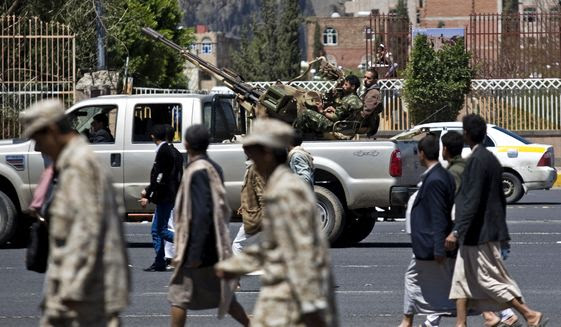 Houthi Shiite fighters (background) patrol as their comrades attend the funeral procession of victims who were killed from triple suicide bombings that hit a pair of mosques in Sanaa, Yemen, on Wednesday. (Associated Press)