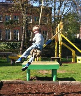 child on rope swing at playground