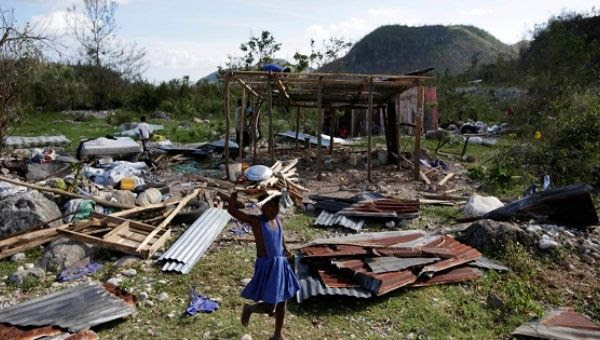 A girl carrying wood walks near debris after Hurricane Matthew passed, in Camp Perrin, Haiti, Oct. 8, 2016.
