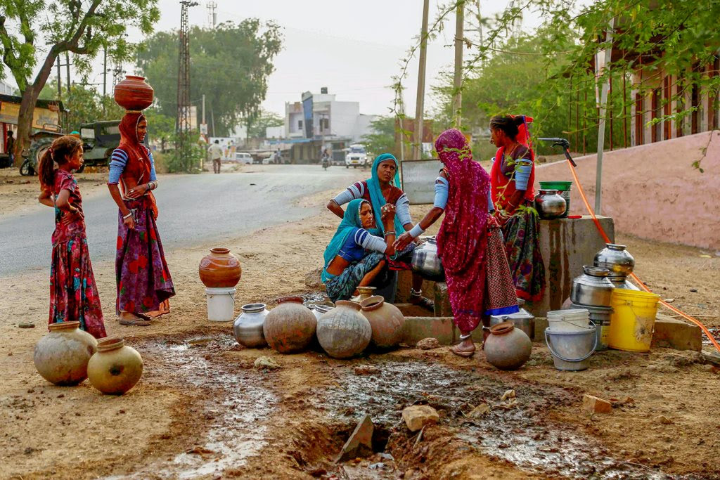 Ajmer: Villagers collect drinking water from a road side water tap during a hot summer day on the outskirts Ajmer, Rajasthan, on Monday. PTI Photo(PTI4_16_2018_000145B)