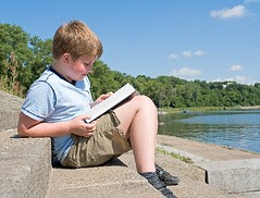 A little boy reads a big book with river by MyTudut, on Flickr