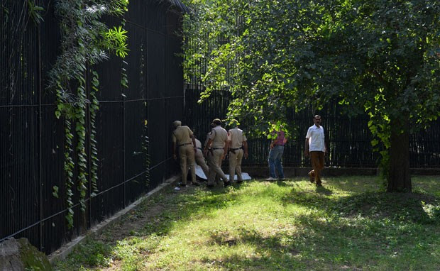 Policiais cercam o corpo do estudante que foi morto por um tigre após entrar em sua jaula no zoológico de Nova Déli (Foto: Chandan Khanna/AFP)