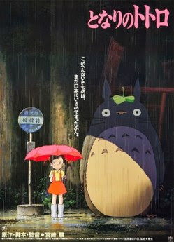 A girl is near a bus stop on a rainy day holding her umbrella. Standing next to her is a large furry creature. Text above them reveals the film's title and below them is the film's credits.