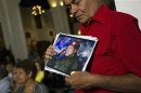 A supporter of Venezuelan President Hugo Chavez holds a picture of him, as he attends a mass to pray for Chavez's health in Caracas