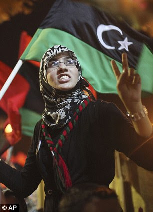 Dreaming of peace: A young woman offers the victory salute following the news of Saif al-Islam's capture
