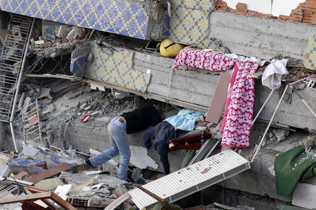 Morador procura por familiares nos escombros de um edifício em Ercim (Foto: Reuters)