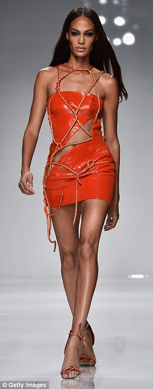 Strappy: The shiny orange material looked as though it was bound together by rope as the frock clung to her every curve as Joan sauntered down the runway