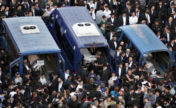 The bodies of Aryeh Kopinsky (C), Calman Levine (L) and Avraham Shmuel Goldberg lie in vehicles during their funeral near the scene of an attack at a Jerusalem synagogue, November 18, 2014. Reuters