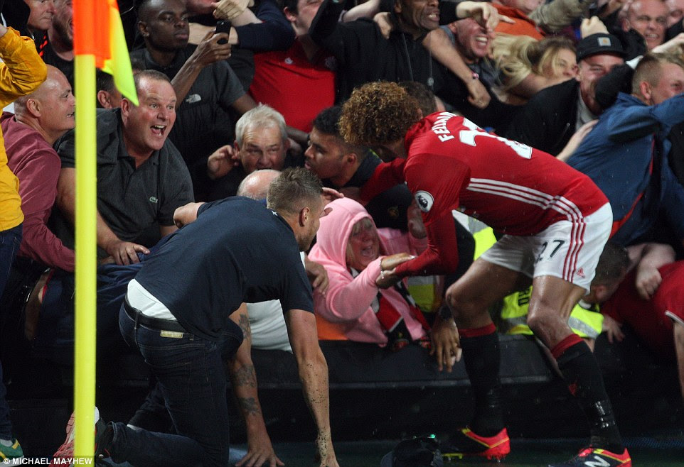 Marouane Fellaini helps a female Manchester United fan during his team's celebrations at Hull
