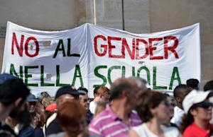 """People hold a banner that reads """" No gender in…"""