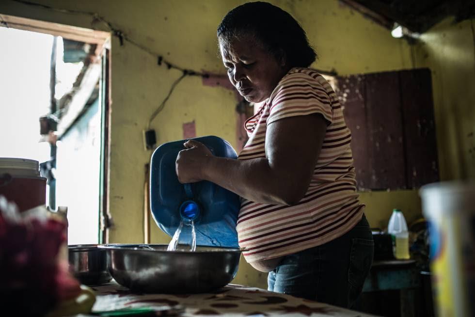 Yaquelín en el interior de su casa, con las garrafas de agua potable que debe transportar desde lo algo para poder cocinar y beber. Barrio de Simón Bolívar, en Santo Domingo.