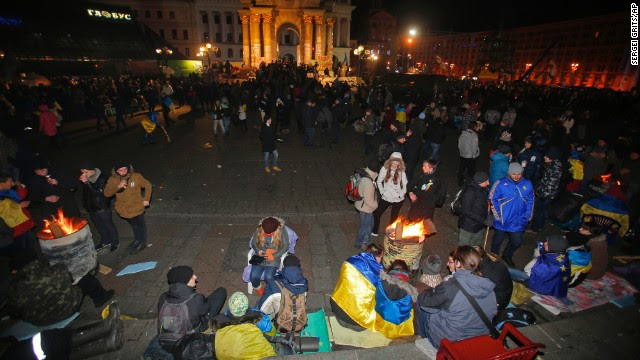 Protesters gather over barrels with bonfires to warm themselves on November 30.