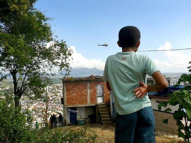 Menino observa ação da Polícia Militar durante ação em comunidades do Espírito Santo. (Foto: André Falcão/TV Gazeta)