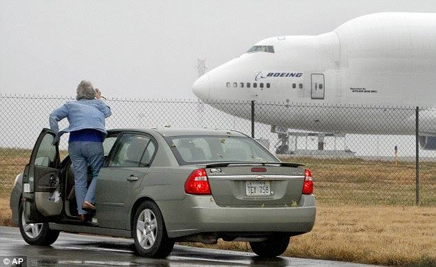 Spectators: A woman tries to take a photo of the Boeing 747 Dreamlifter which mistakenly landed at Col James Jabara Airport in Wichita, Kansas, and is currently stuck there