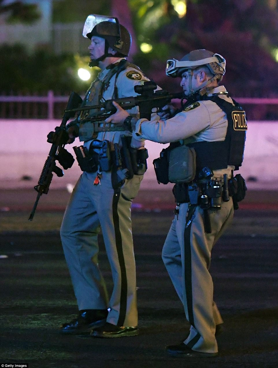 Las Vegas Metropolitan Police Department officers point their weapons at a car driving down closed Tropicana Ave. near Las Vegas Boulevard after a mass shooting at a country music festival nearby on October 2, 2017 in Las Vegas, Nevada