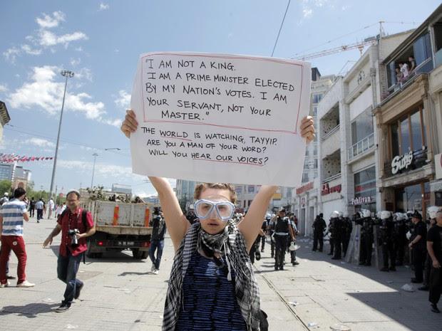 Manifestante empunha cartaz com frases contra o primeiro-ministro turco: 'Eu não sou um rei, eu sou um primeiro-ministro eleito pelo povo. Sou seu servo, não seu mestre.' (Foto: Gurcan Ozturk/AFP)