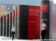 Exhibition of huge Brockhaus books with women weaving inbetween
