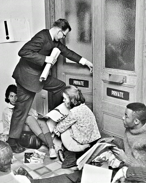 Description of  MAR 9 1965 - FBI Clerk Steps Over Sit-In Group. Demonstrators sat in the hallway of the Denver FBI office for more than five hours Tuesday in a request for sterner federal protection for Alabama race marchers. An FBI investigative clerk here steps over the feet of Mrs. Mamie Whitley, 2295 E. Iliff Ave., left, and Mrs. Sharon Wanner, 2524 S. University Blvd. (David Mathias/The Denver Post)