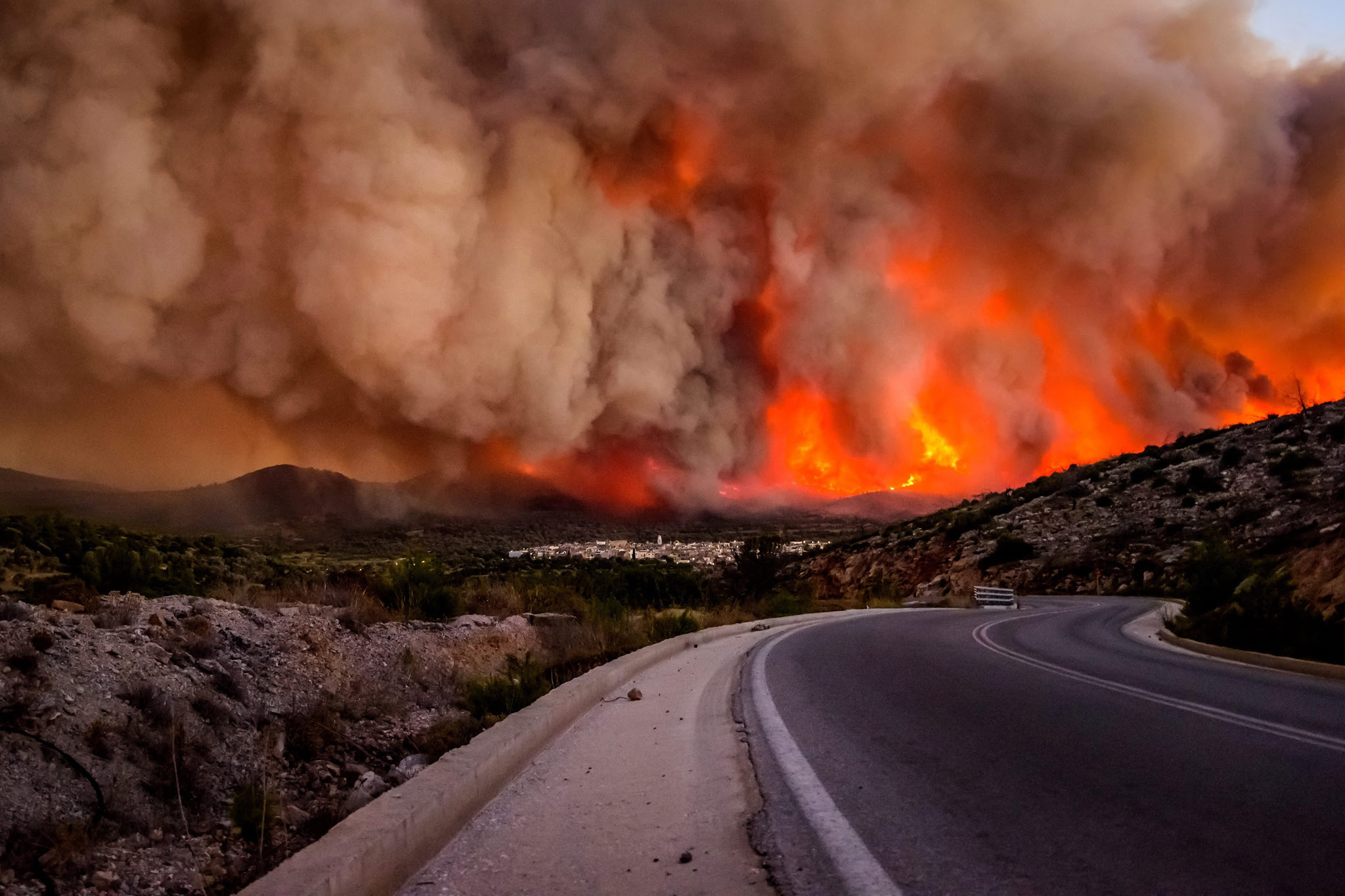 A picture made available on 26 July 2016 shows dense smoke over Lithi village  during a wildfire on Chios island, Greece, 25 July 2016. The huge wildfire that broke out early 25 July 2016, on the island of Chios which has burned 3,500 hectares of forest and farm land, set under control. Over 90 percent of the mastic trees at the villages of Lithi, Elata and Vessa were destroyed while a large number of mastic trees were burned at the villages of Mesta, Armolia and Pyrgi.  EPA/KOSTAS KOYRGIAS